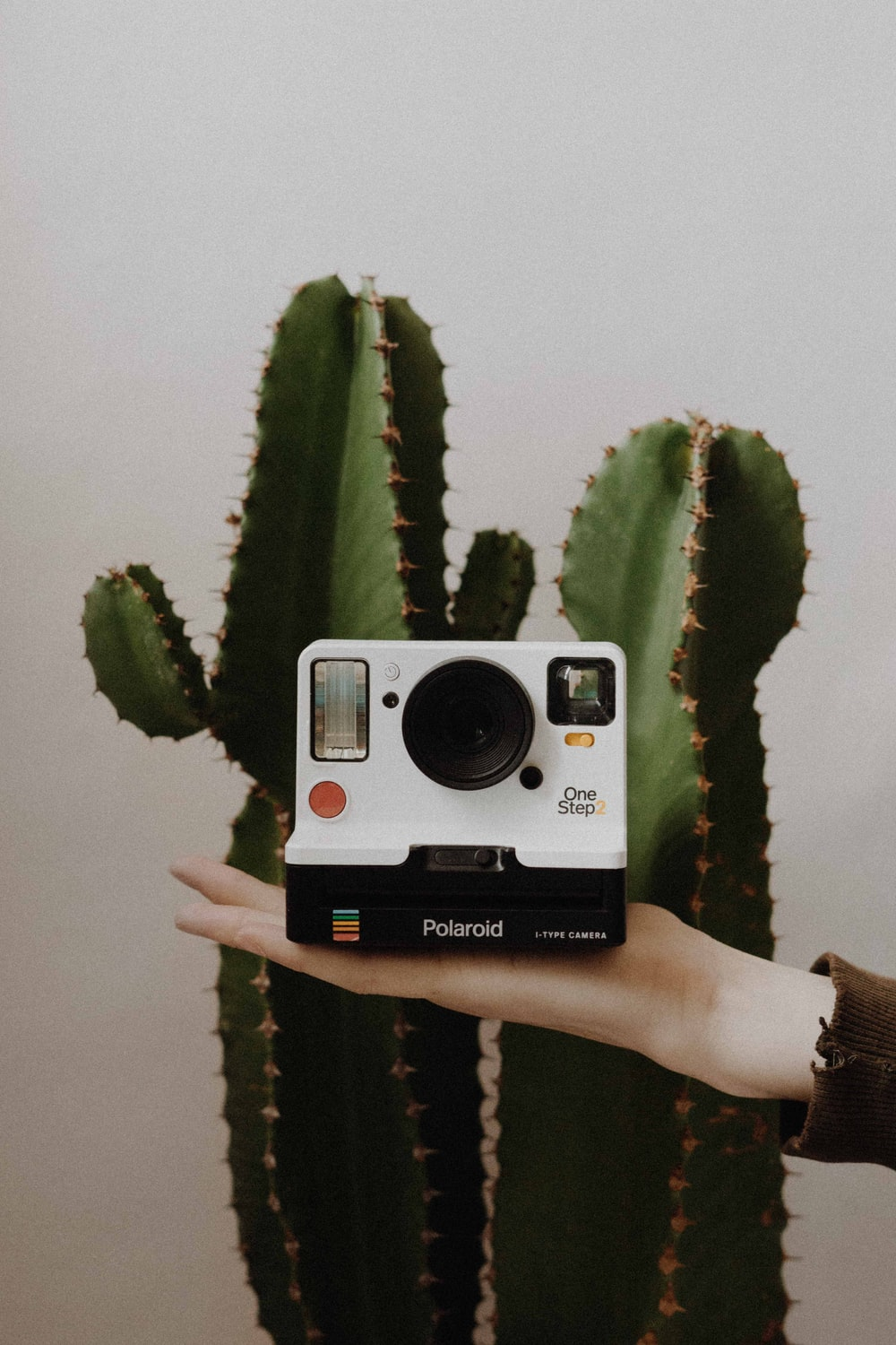 white and black Polaroid One Step instant camera