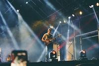 man playing guitar on stage during nighttime