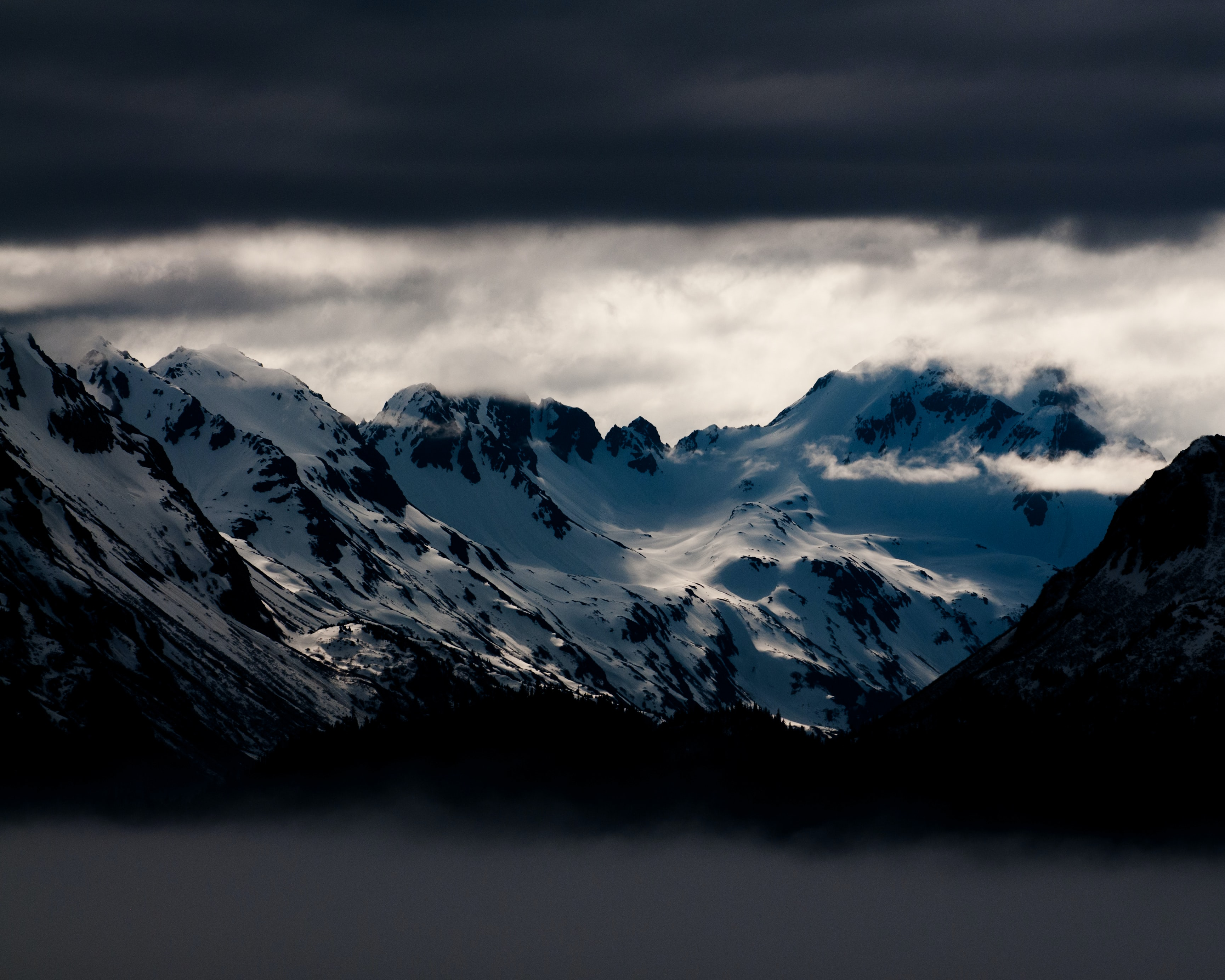 snow covered mountains under white clouds at daytime