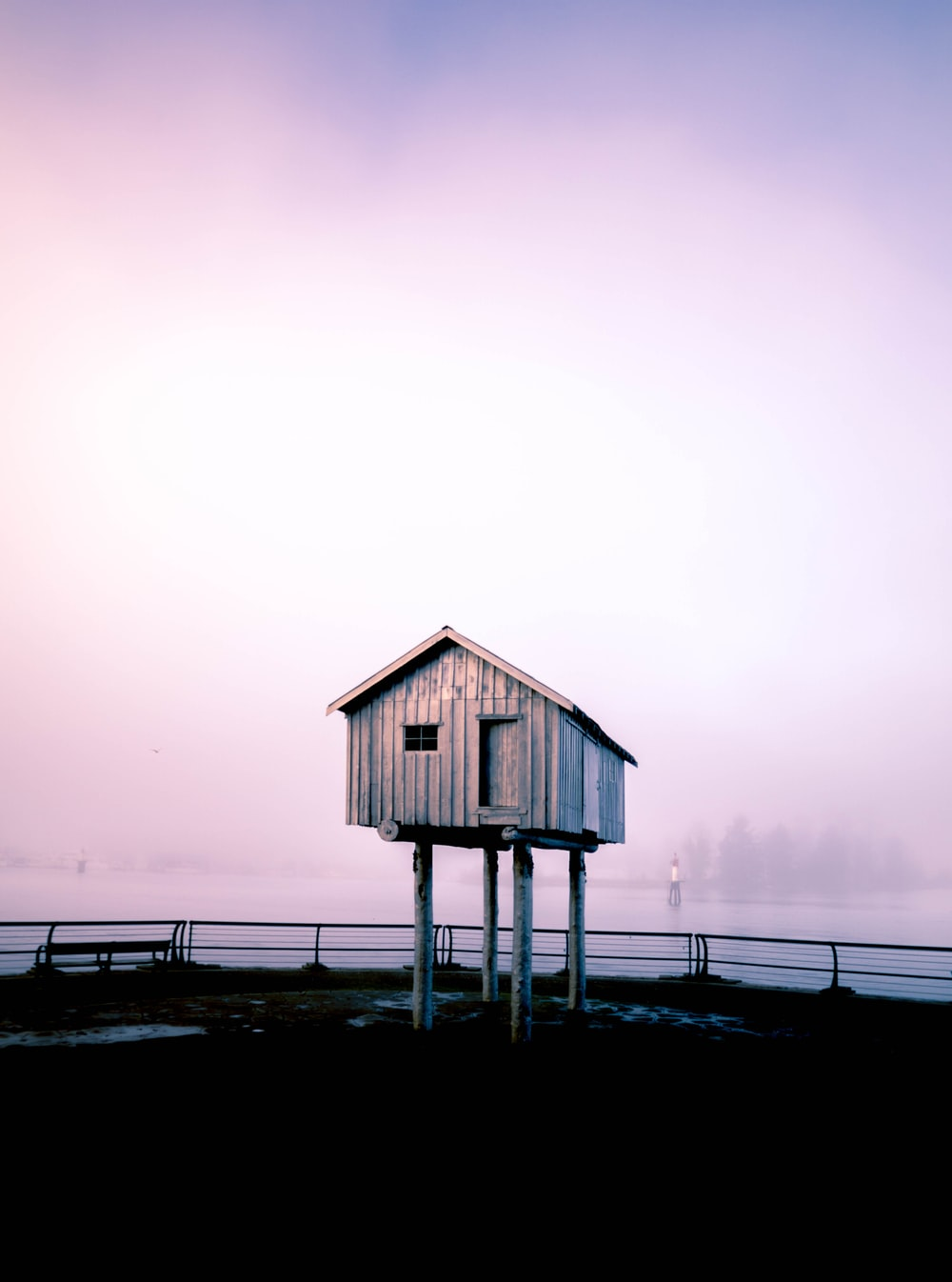gray wooden storage shed under gray sky