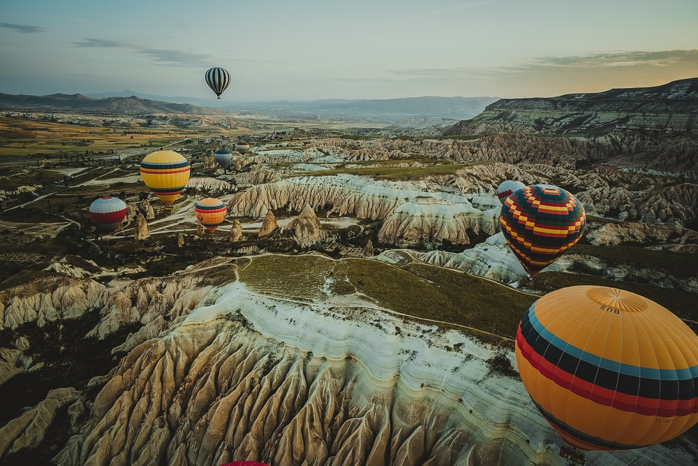 assorted-color hot air balloons on mid-air during orange sunset