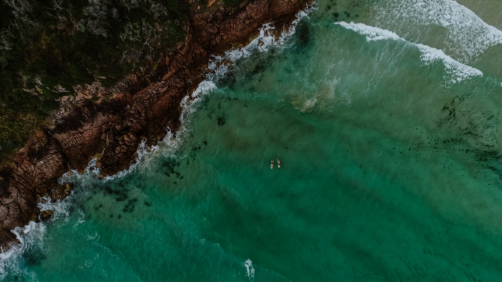 Aerial View Photography Of Green Ocena Water Near Seashore During Daytime