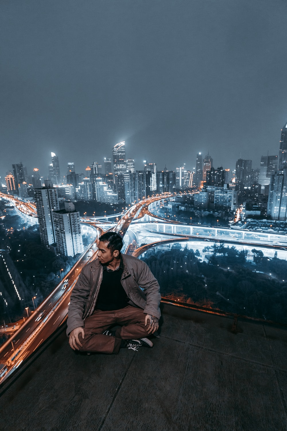 man sitting on rooftop looking his right side during night time