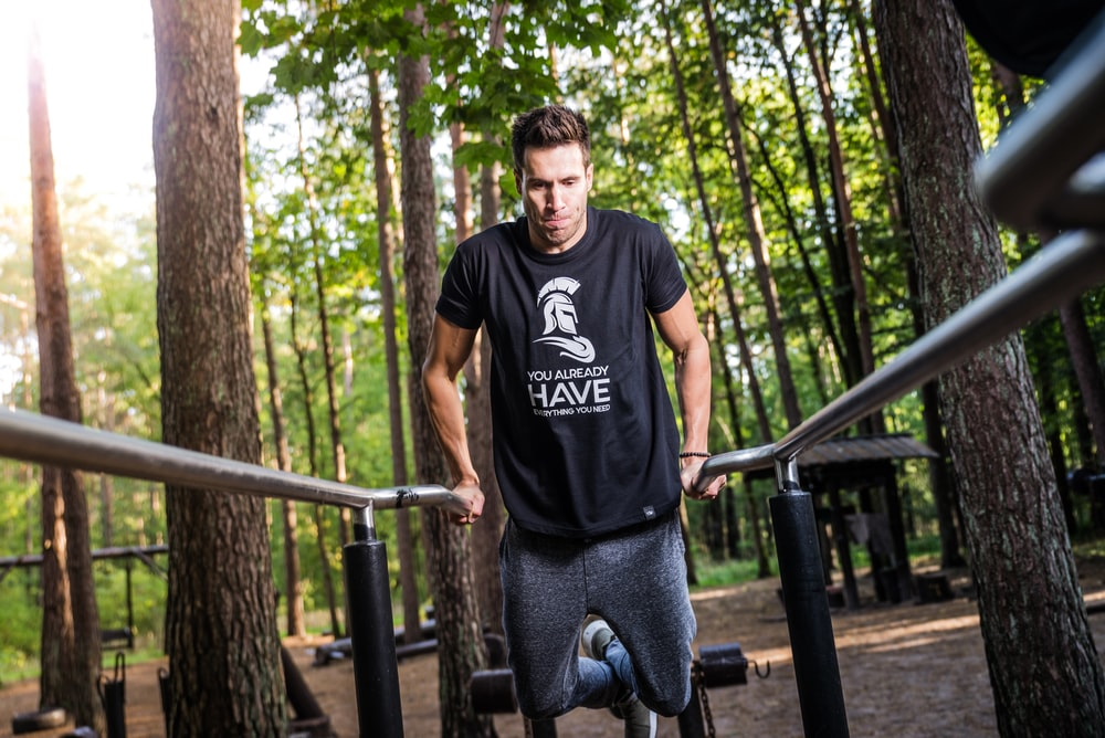 person doing dips on gray rails under shade of trees during daytime