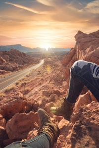 person sitting on rock formation cliff
