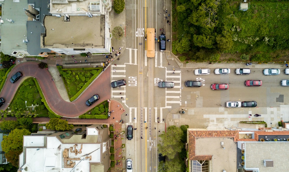 aerial photography of people and vehicles on cross road
