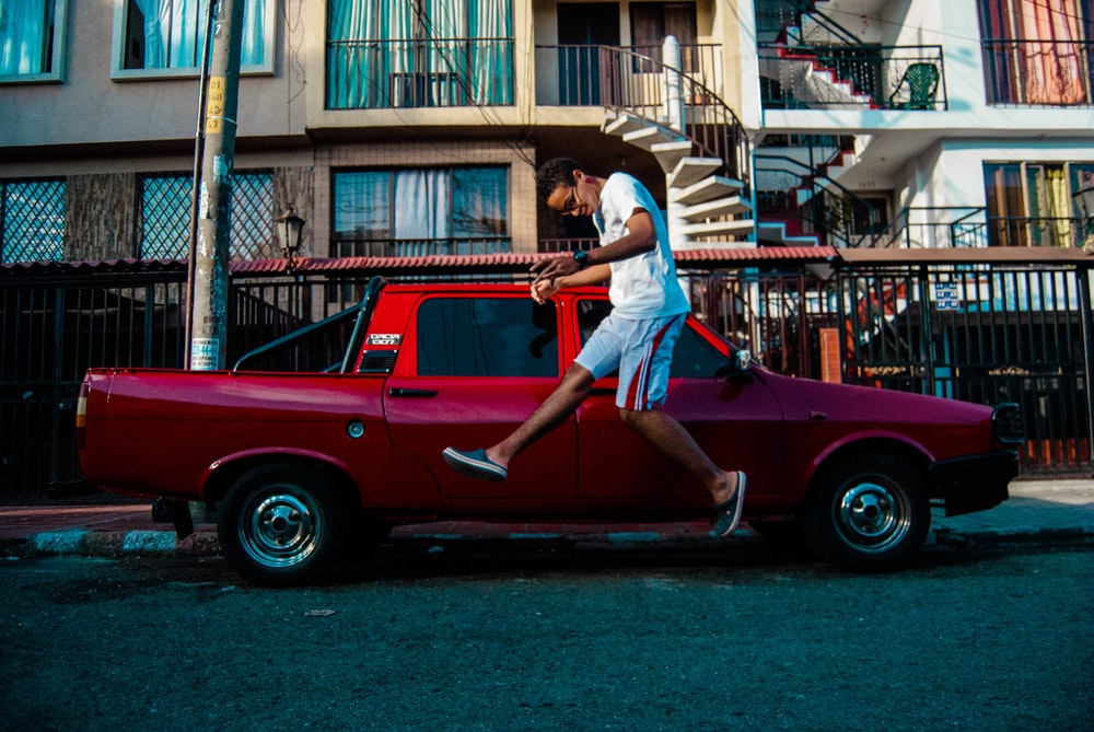 man jumping beside red pickup truck