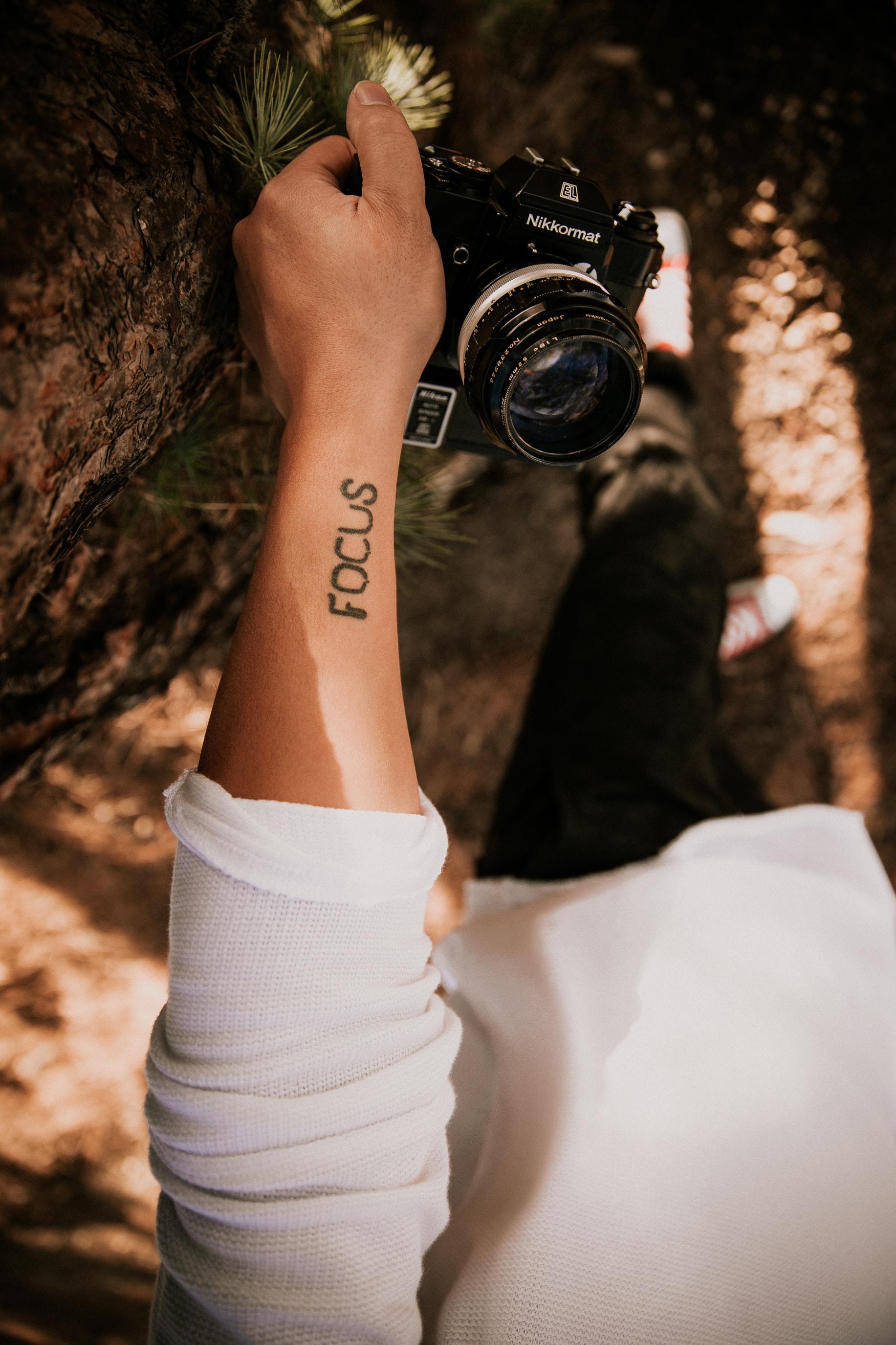 person holding black Nilkormat SLR camera