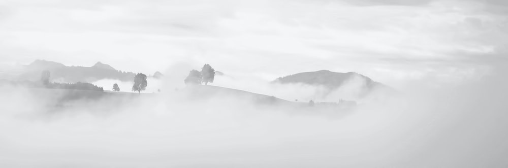 grayscale photography of foggy mountain