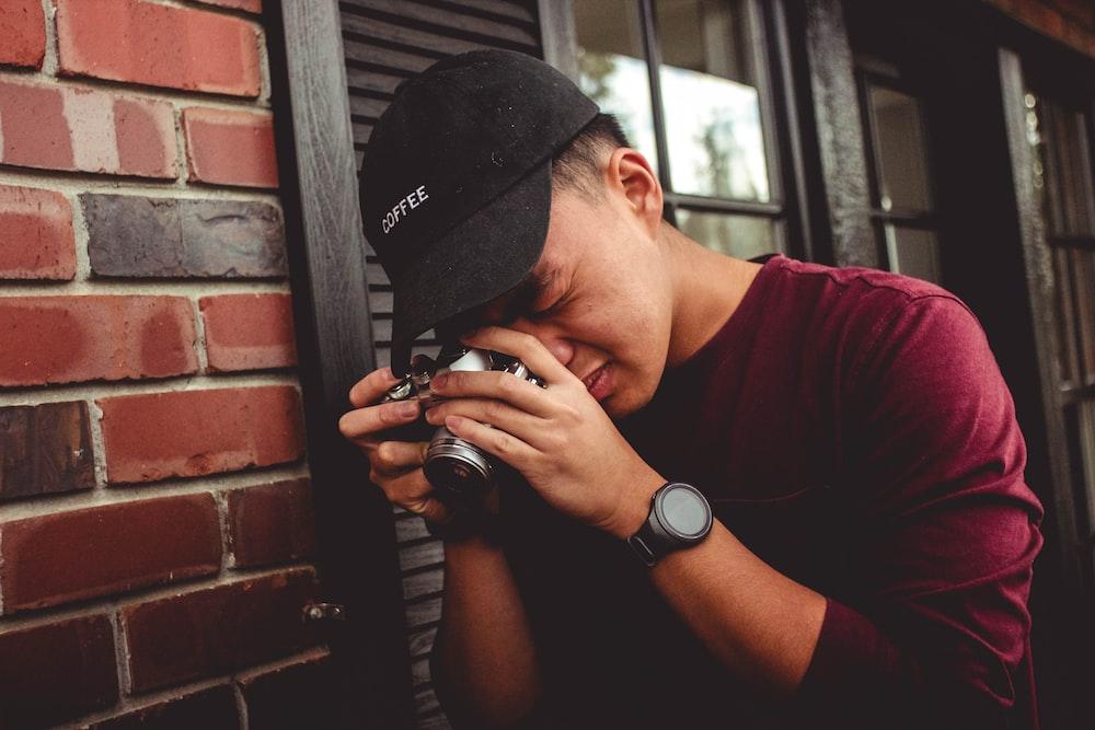 man leaning on wall holding camera near window