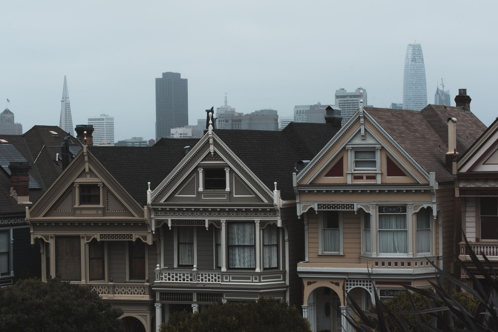 three gray and beige concrete houses under cloudy sky at daytime