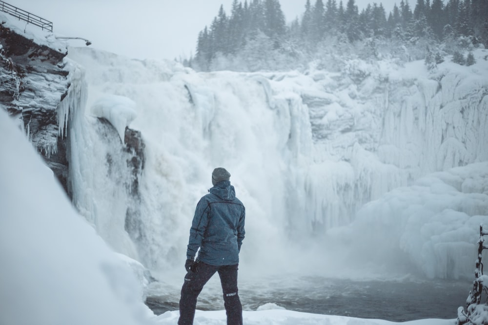 man standing near snow covered falls during daytime