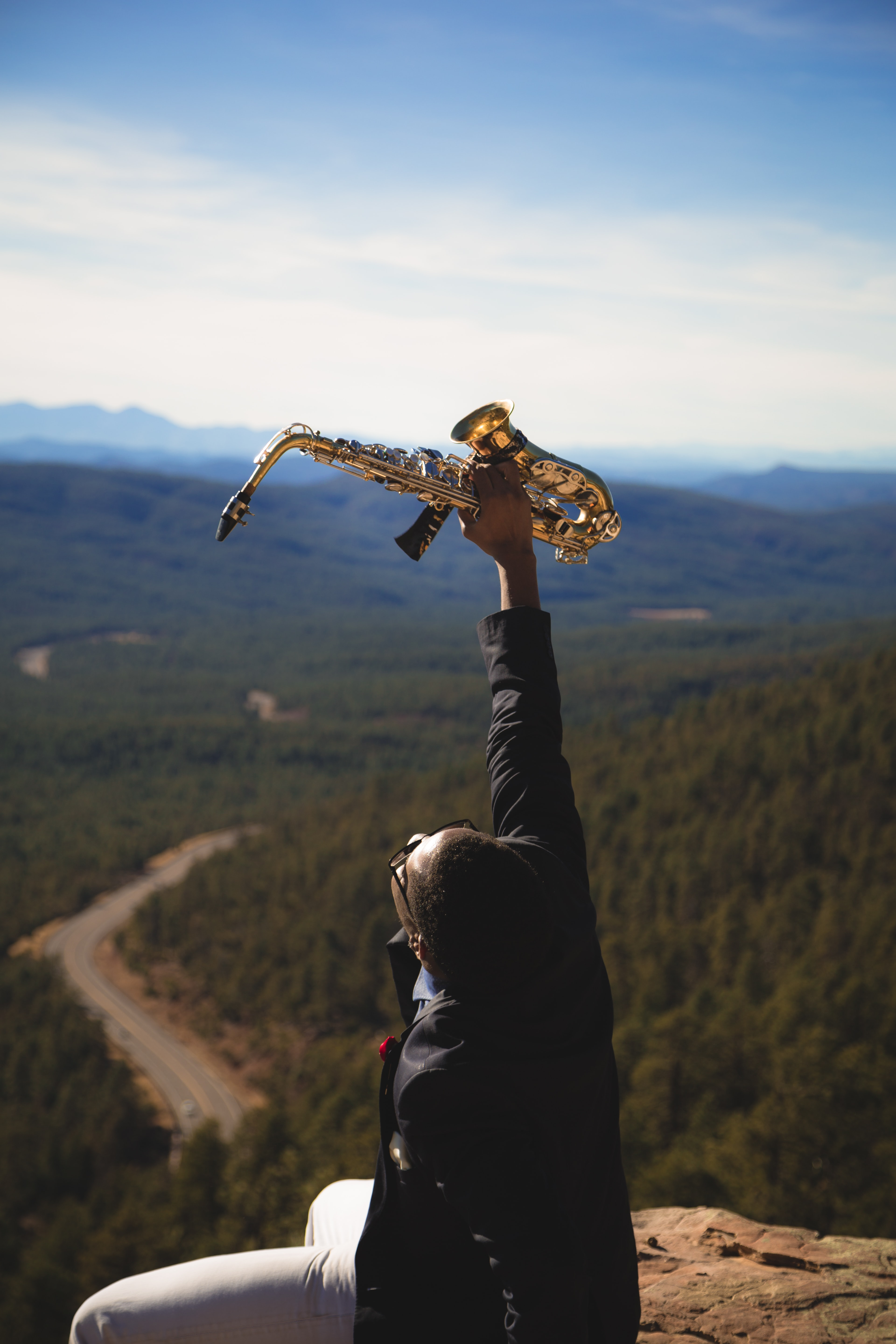 person holding up brass-colored saxophone