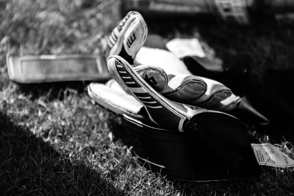 greyscale photo pair of gloves on grass field