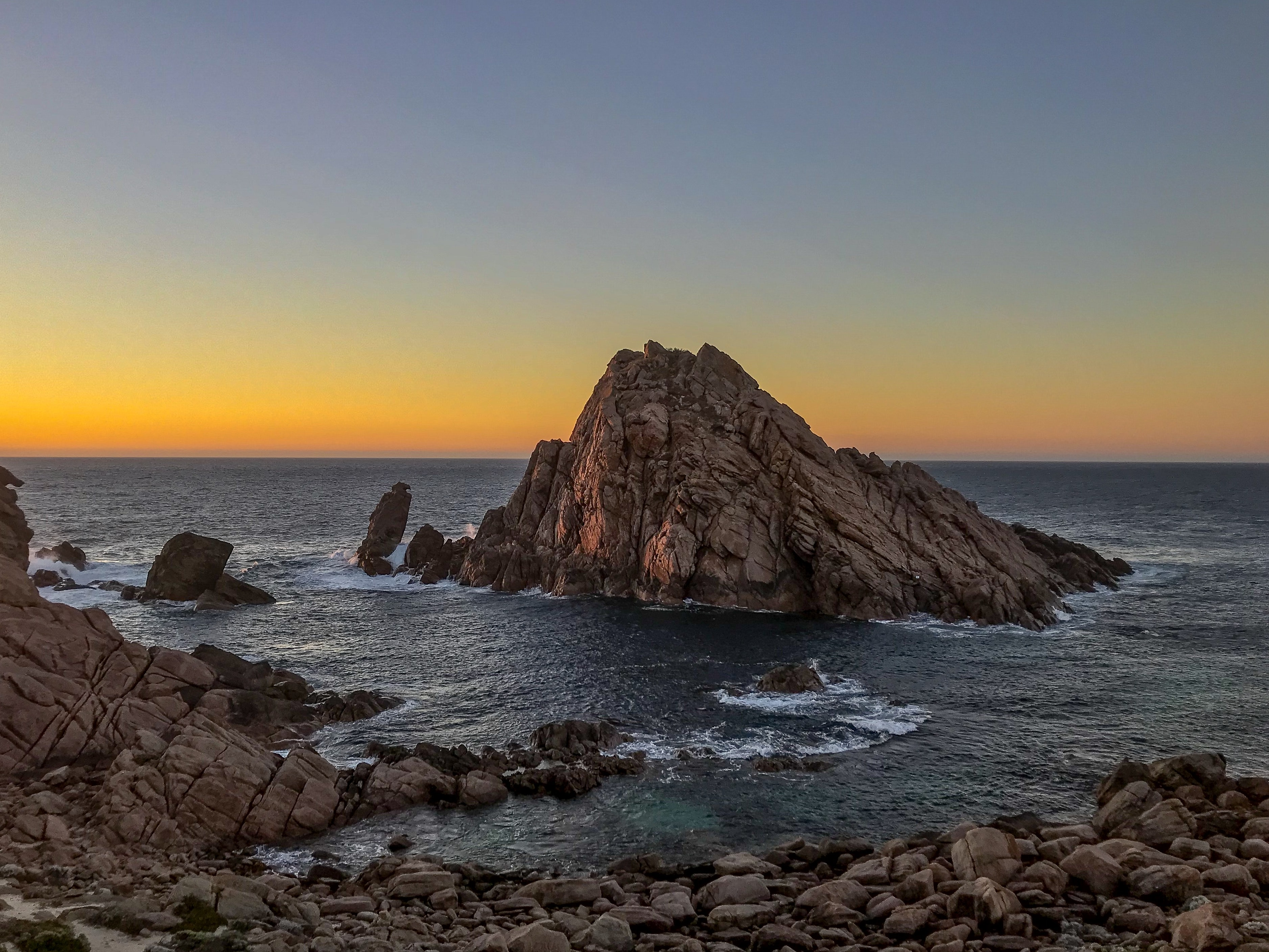 rock formation on sea during sunset