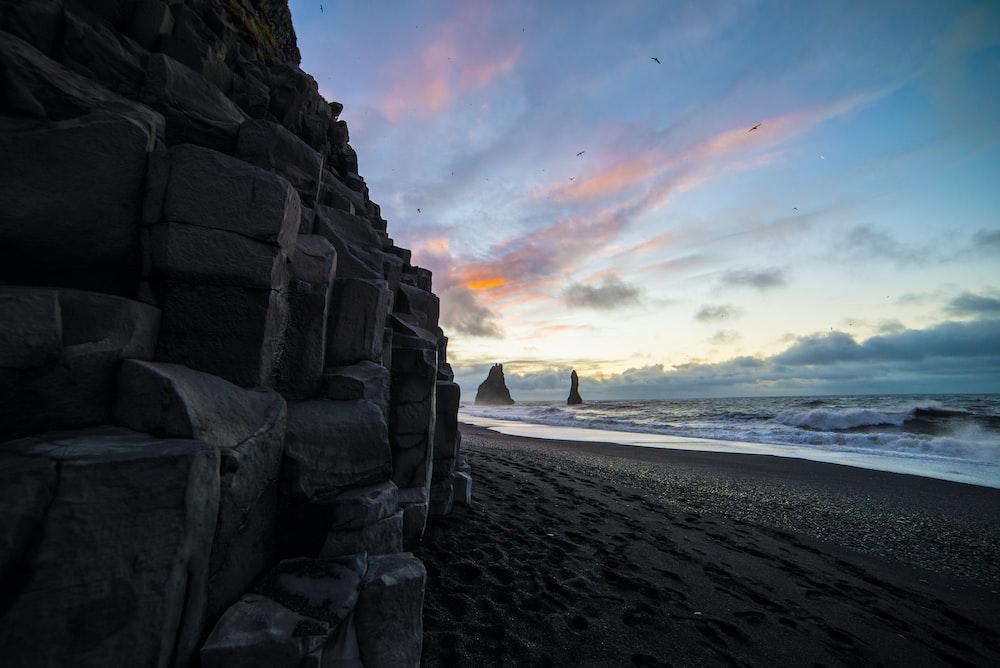 brown rock formation near sea