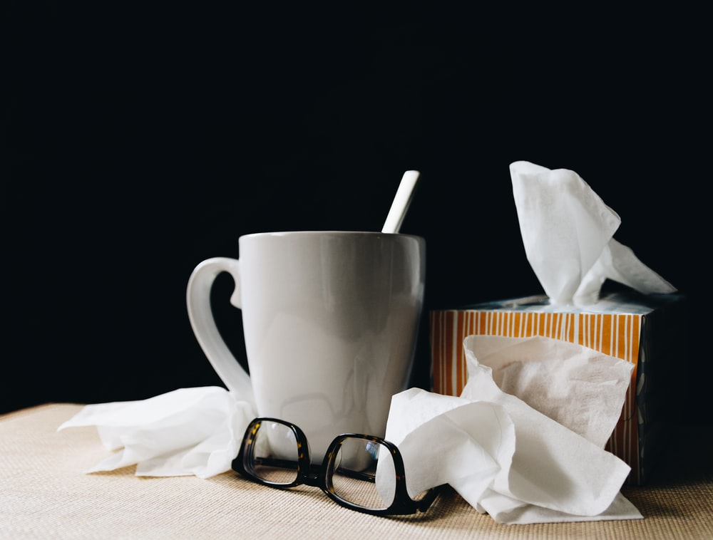 white ceramic mug on white table beside black eyeglasses