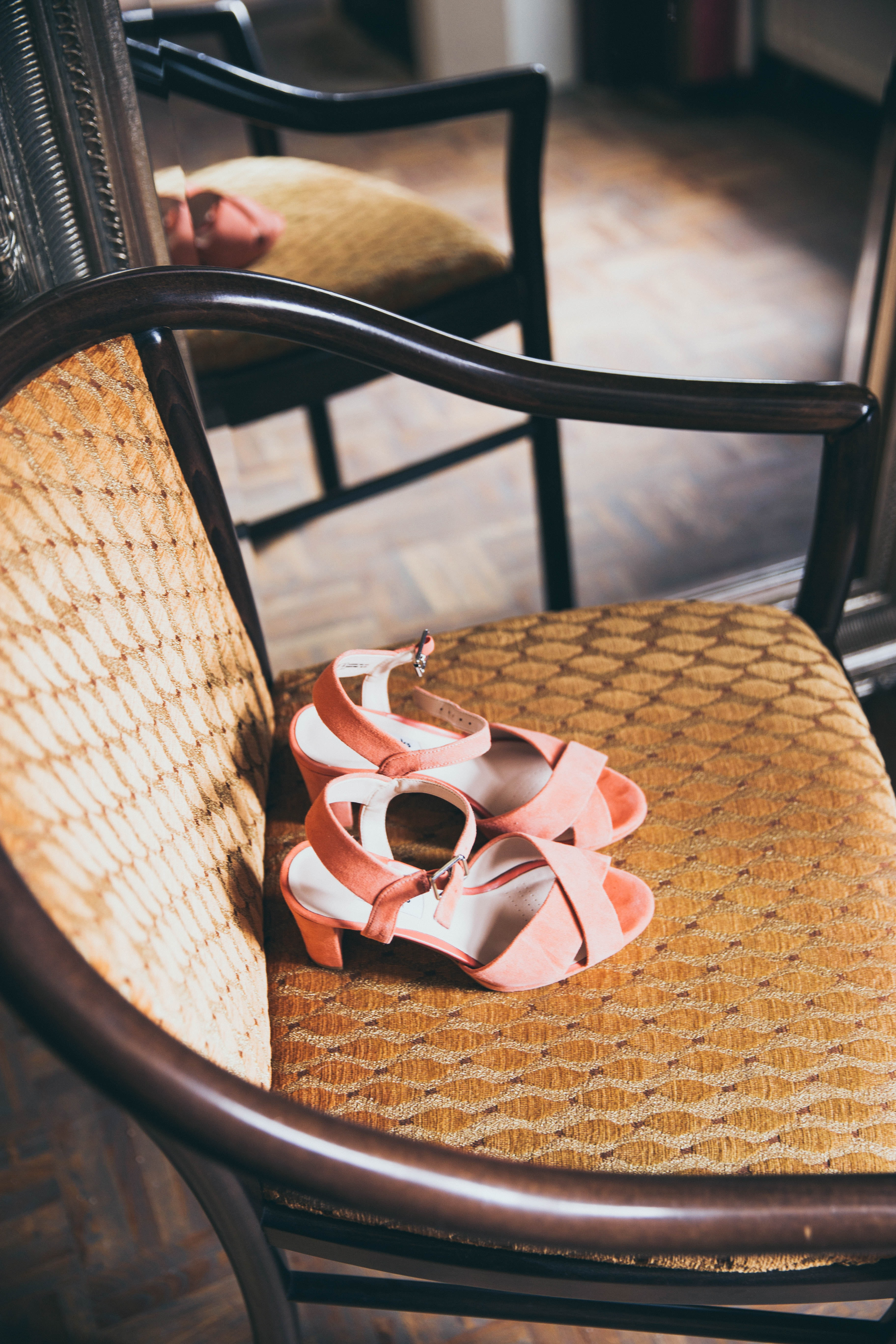 pair of pink suede peep-toe chunky-heels sandals on beige wooden armchair