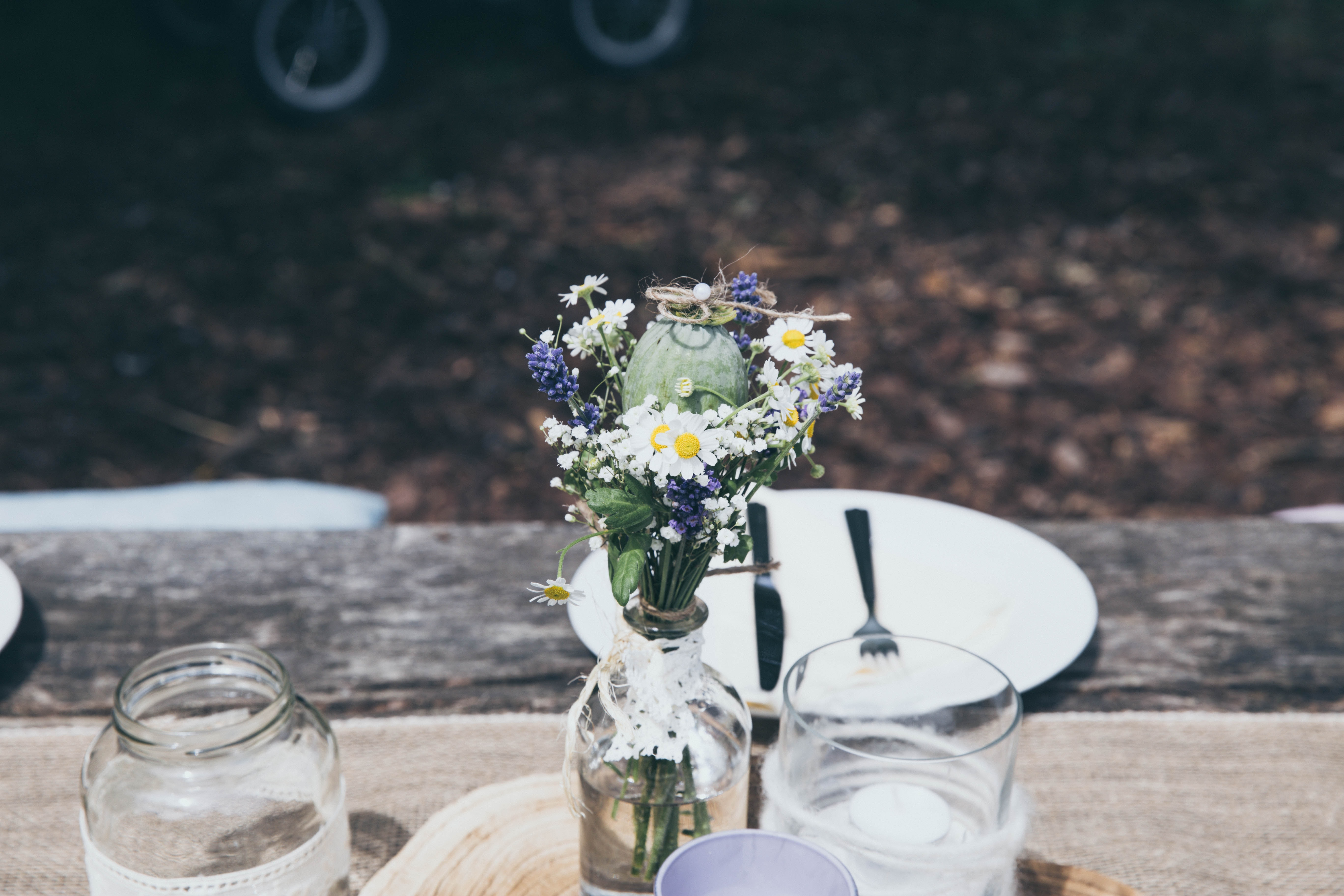 white and blue flowers in clear glass bottle