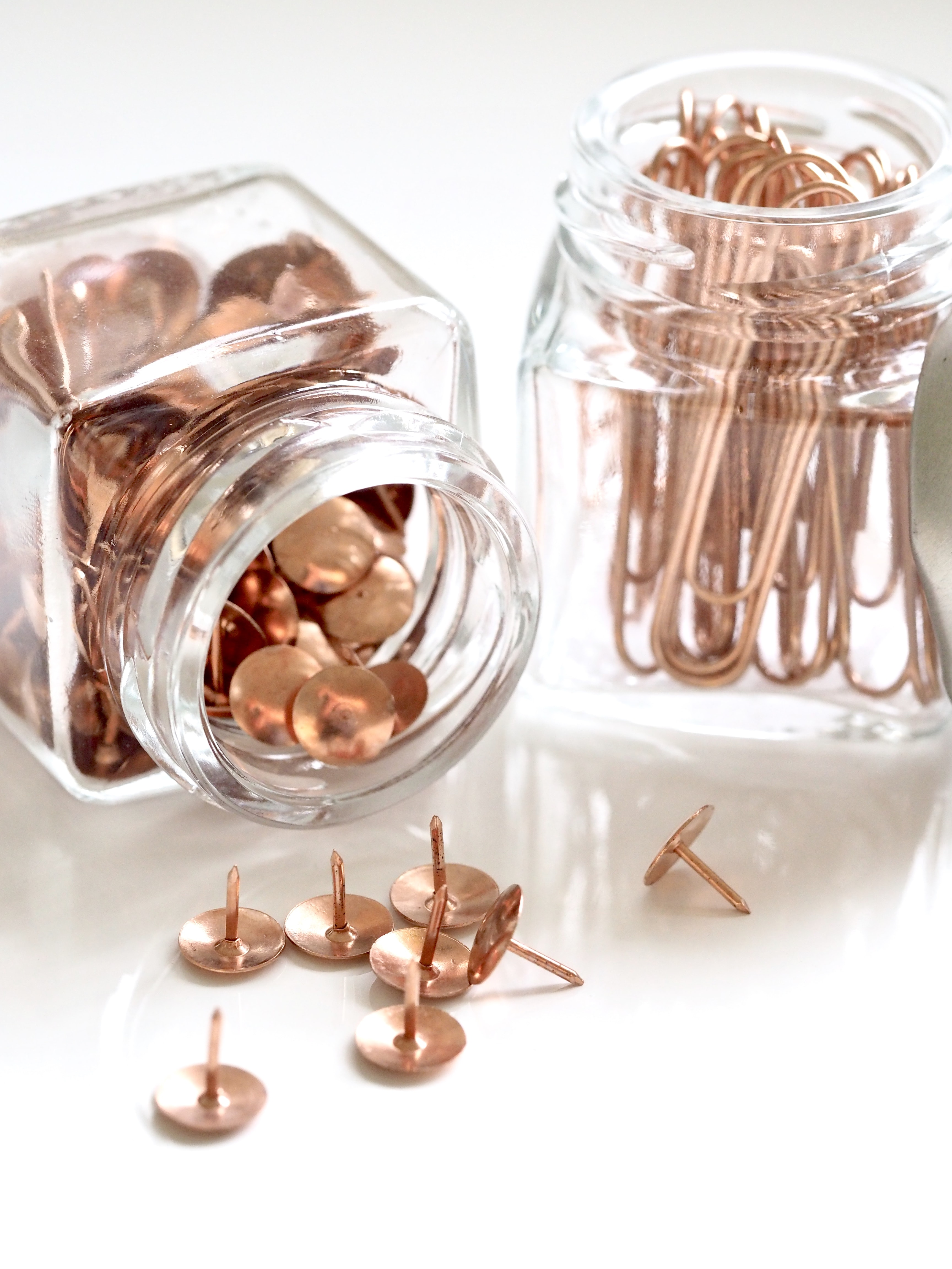 photo of bronze-colored thumb tacks and paper clips in clear glass bottles