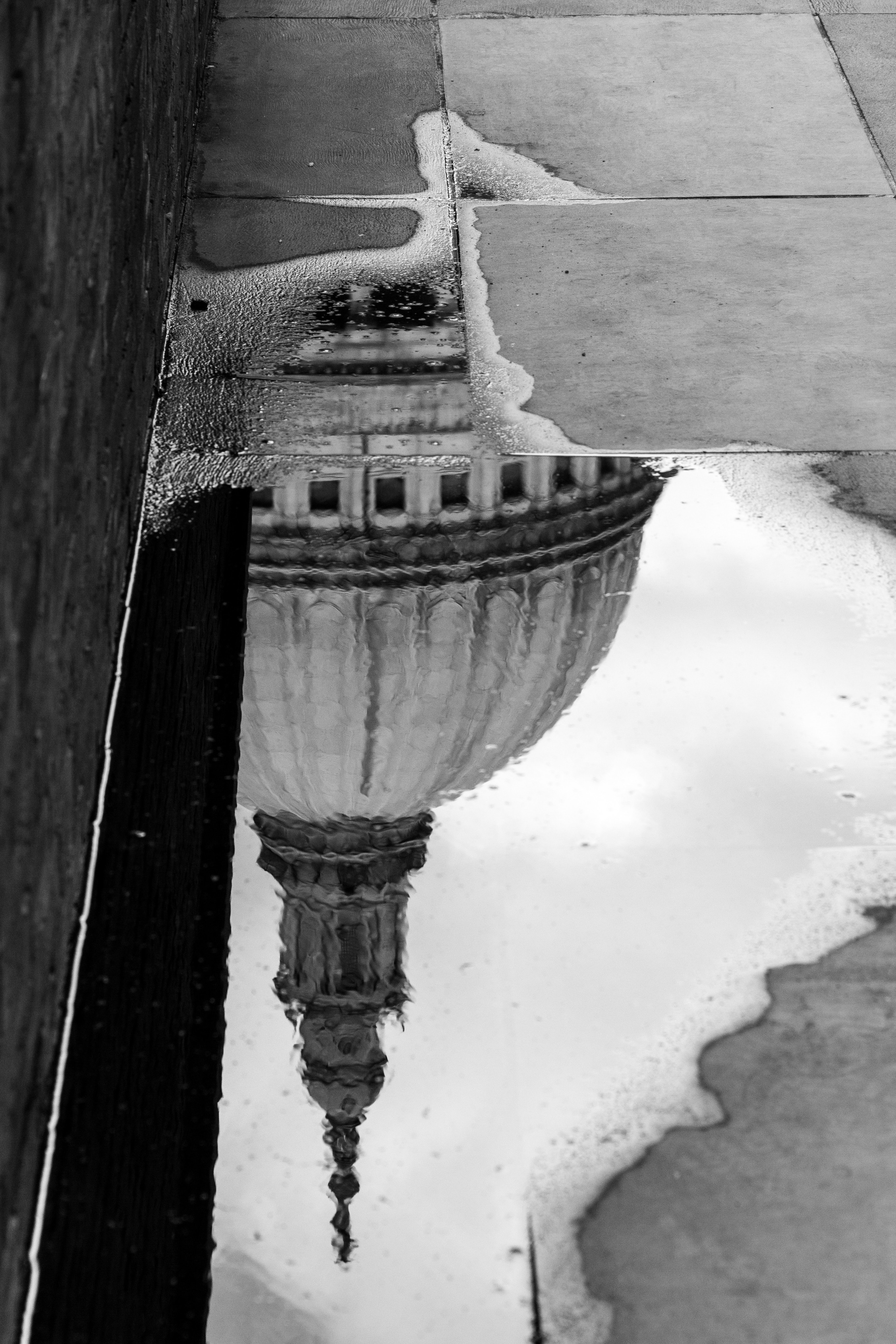 grayscale photo of puddle on sidewalk