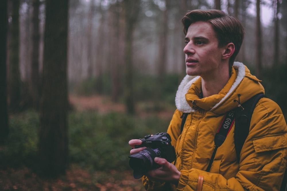 man wearing yellow parka jacket holding DSLR camera