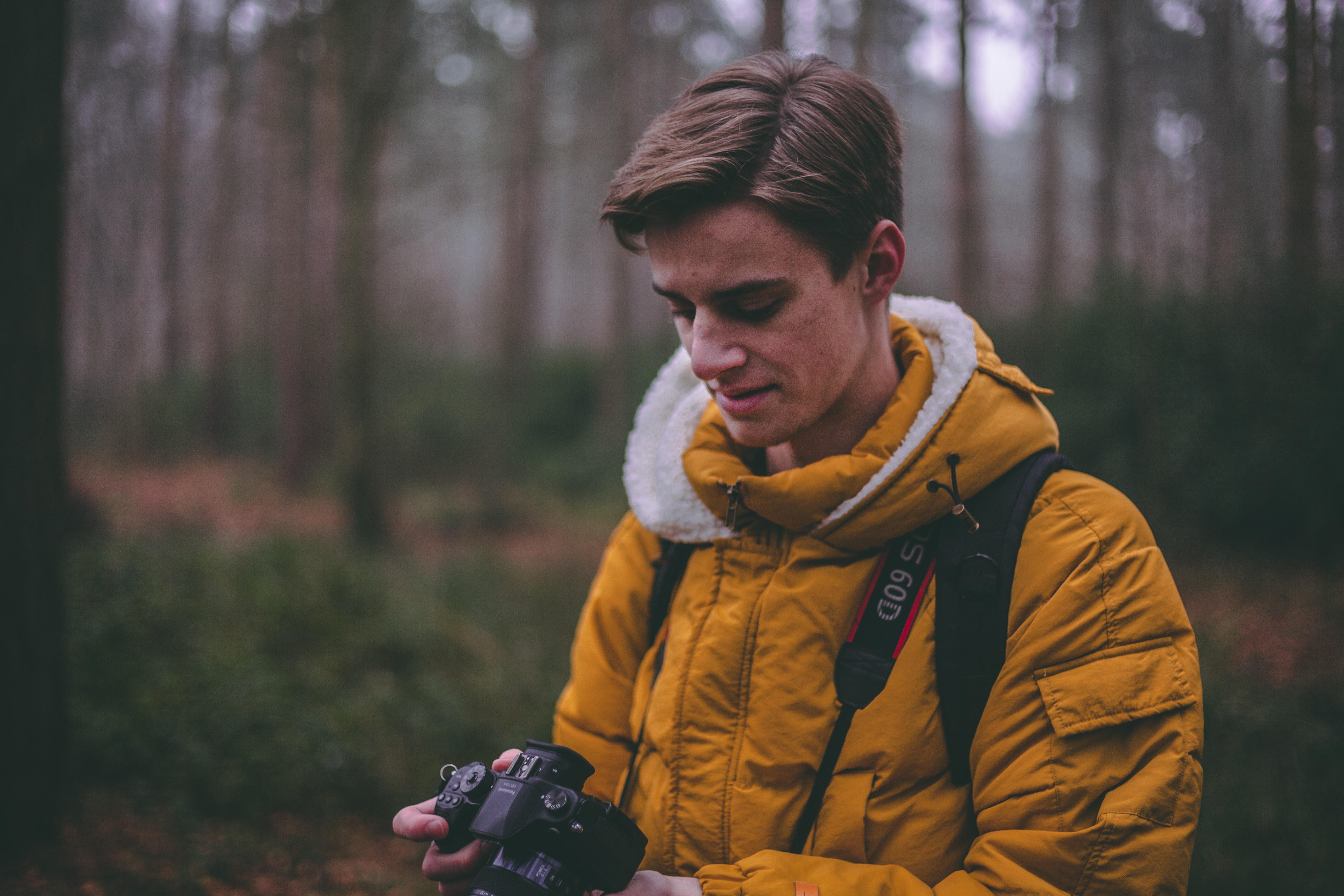 man standing holding DSLR on forest