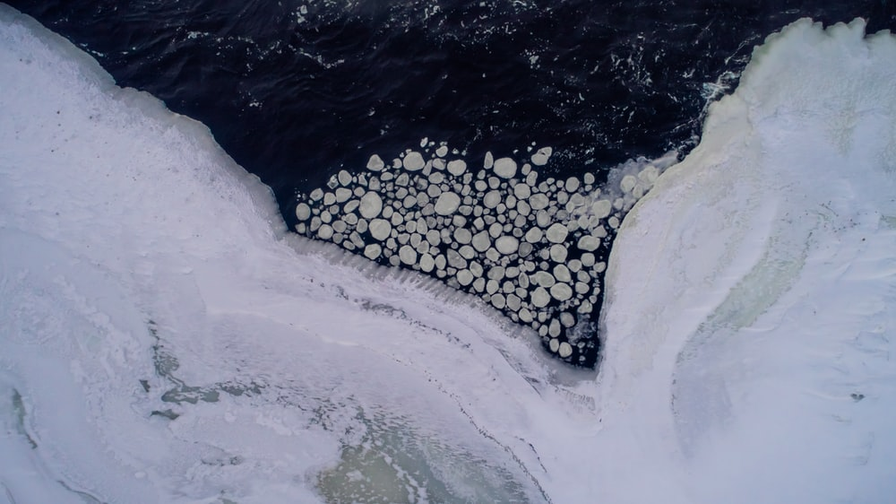 aerial photo of body of water near snow covered road