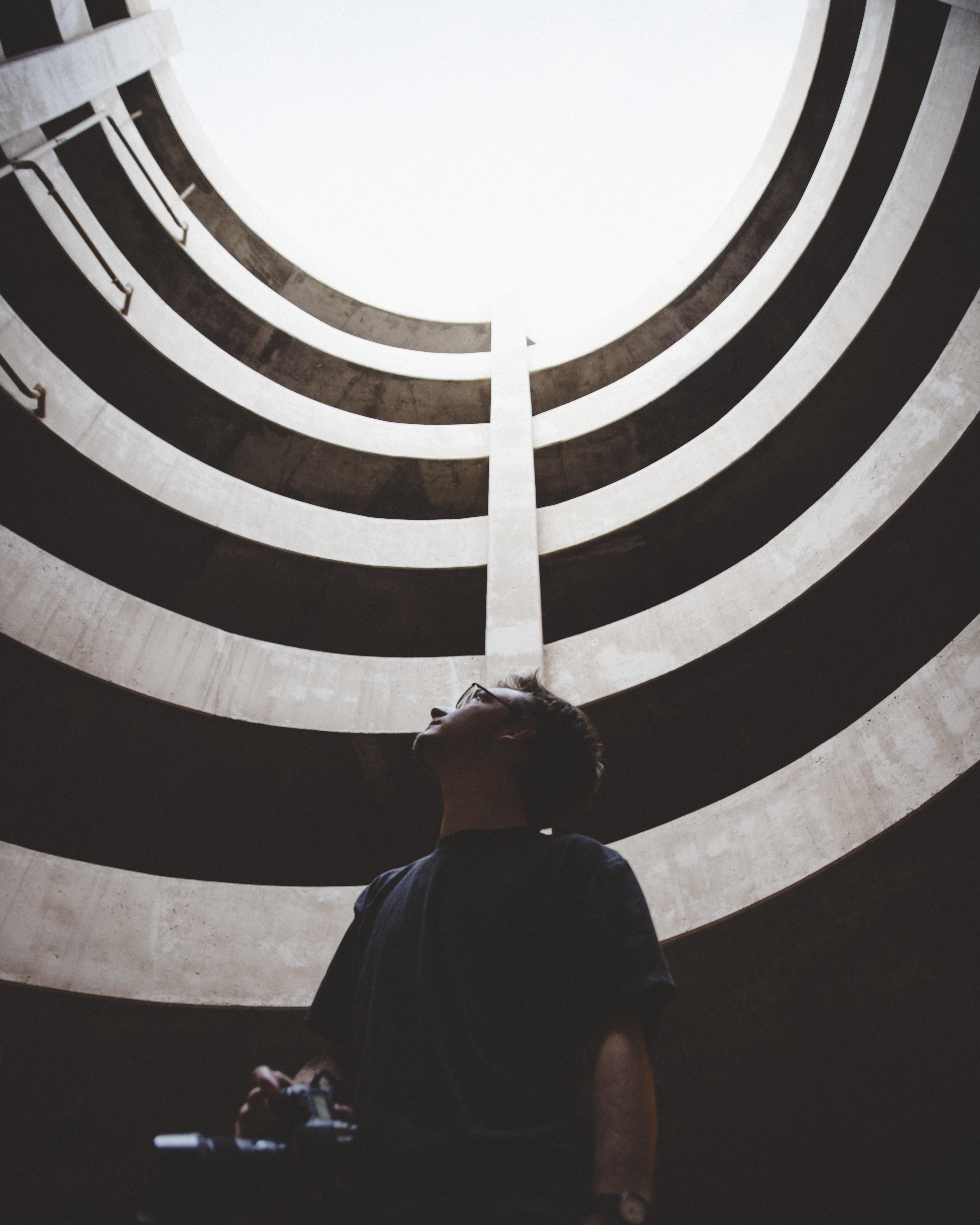 man in blue crew-neck t-shirt holding black DSLR camera looking up inside brown building