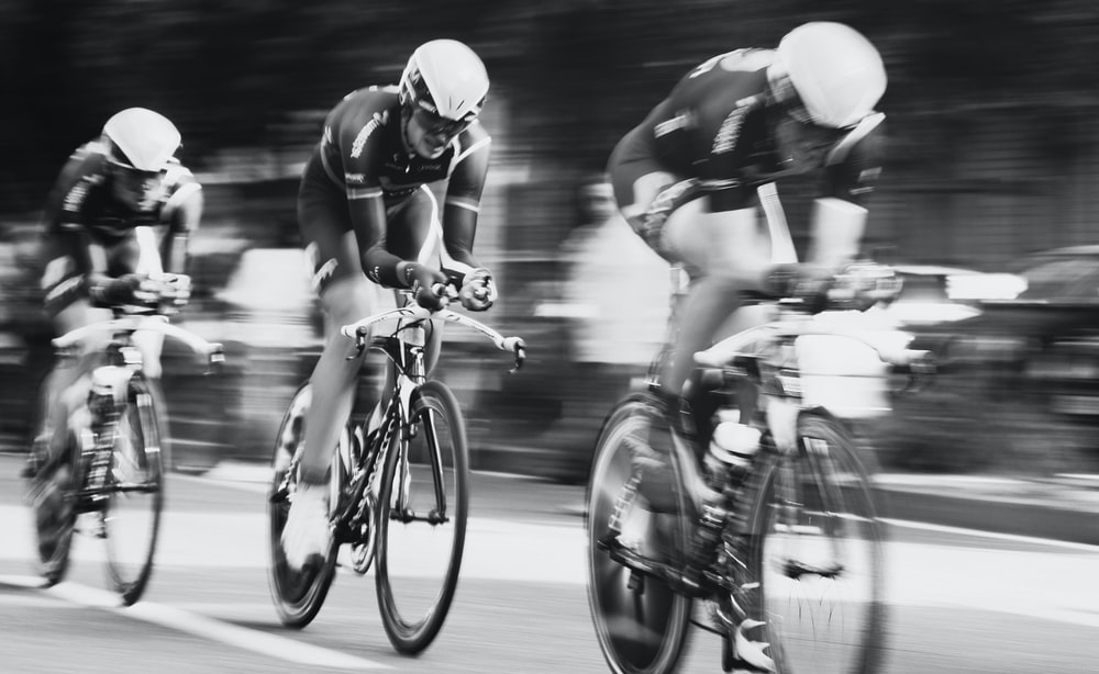 time lapse photography of three men cycling