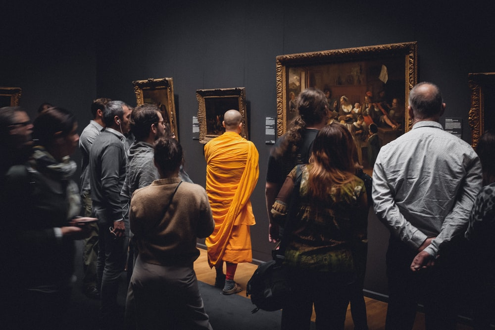 people standing in front of paintings