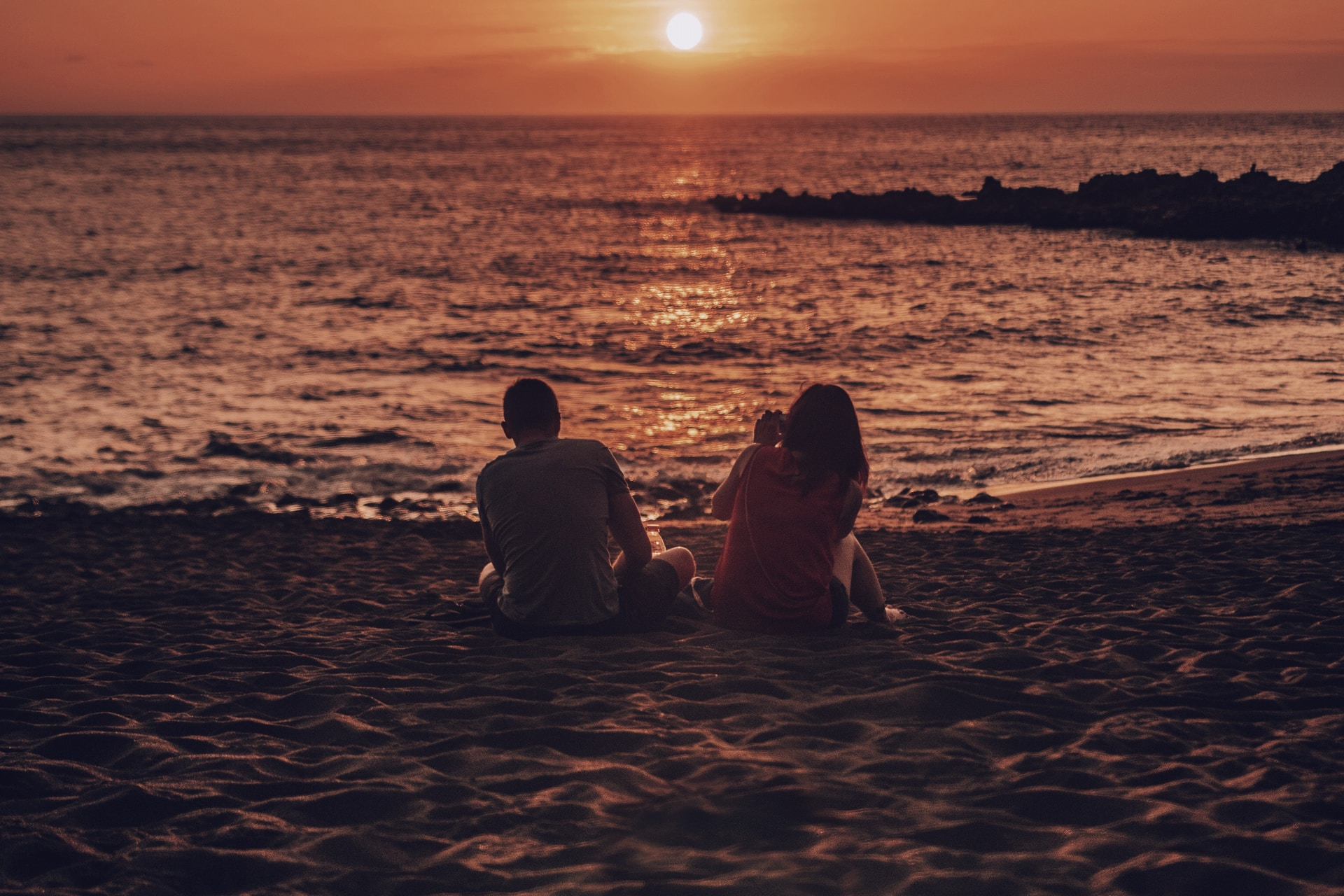 man and woman sitting on beach during golden hour