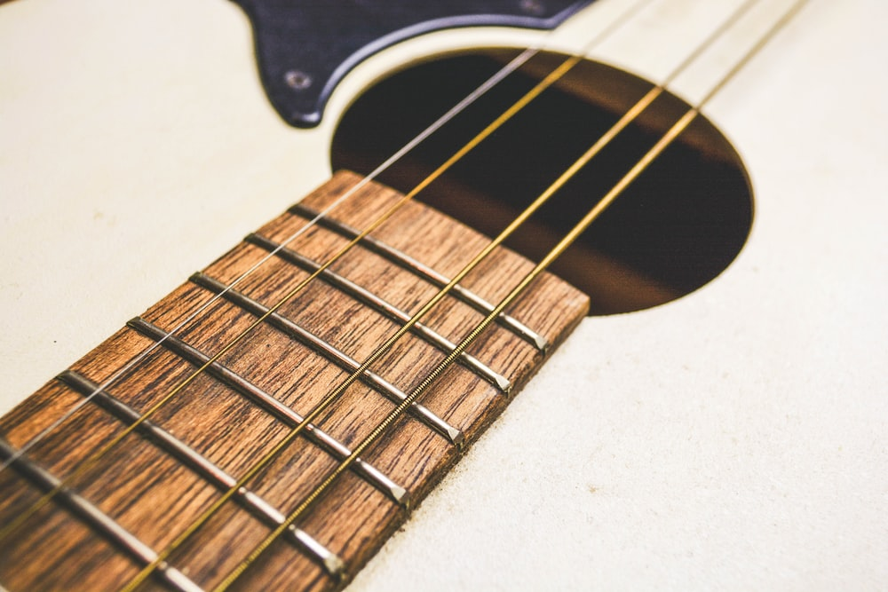 beige and brown acoustic guitar