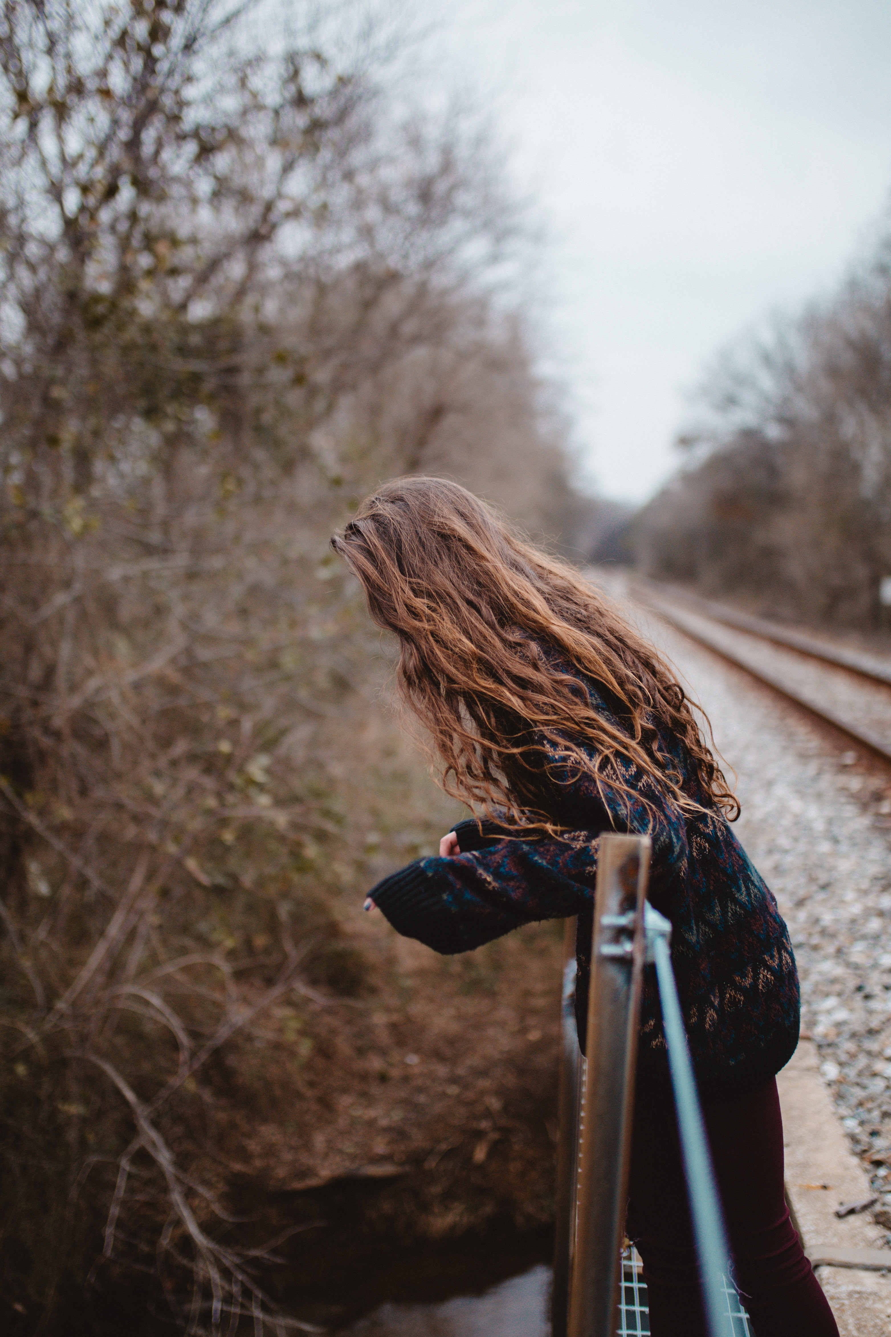 woman leaning on brown and gray railings near bare forest