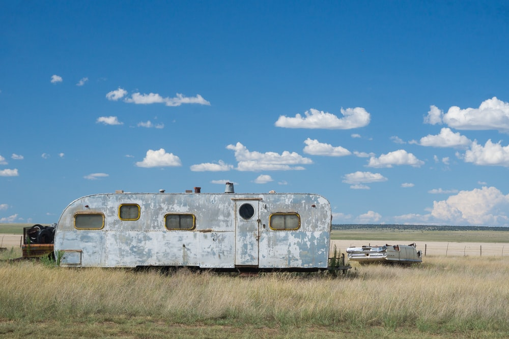 gray metal travel camper on grass land under blue and white cloudy skies at daytime