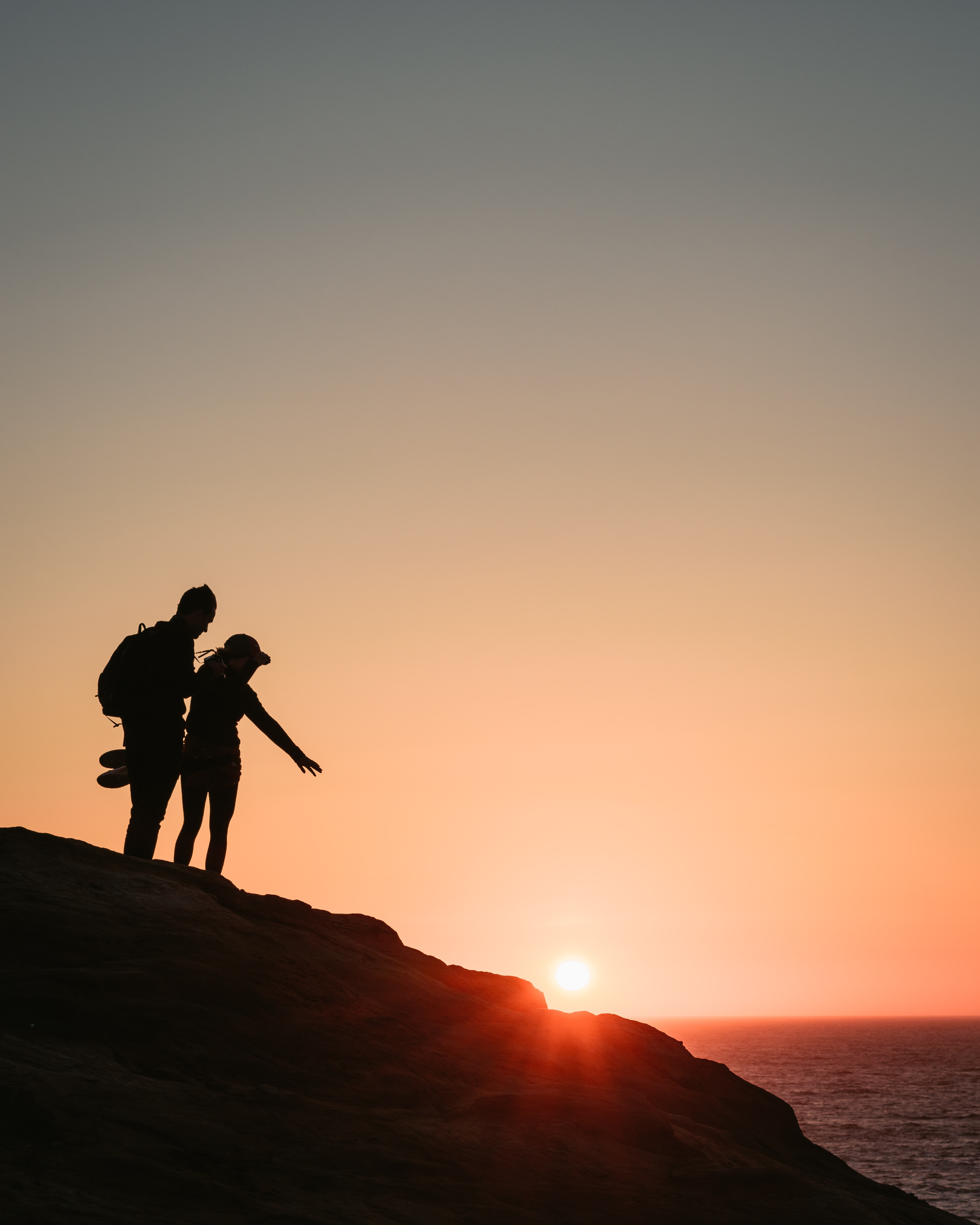 silhouette of man and woman standing on rock formation near body of water