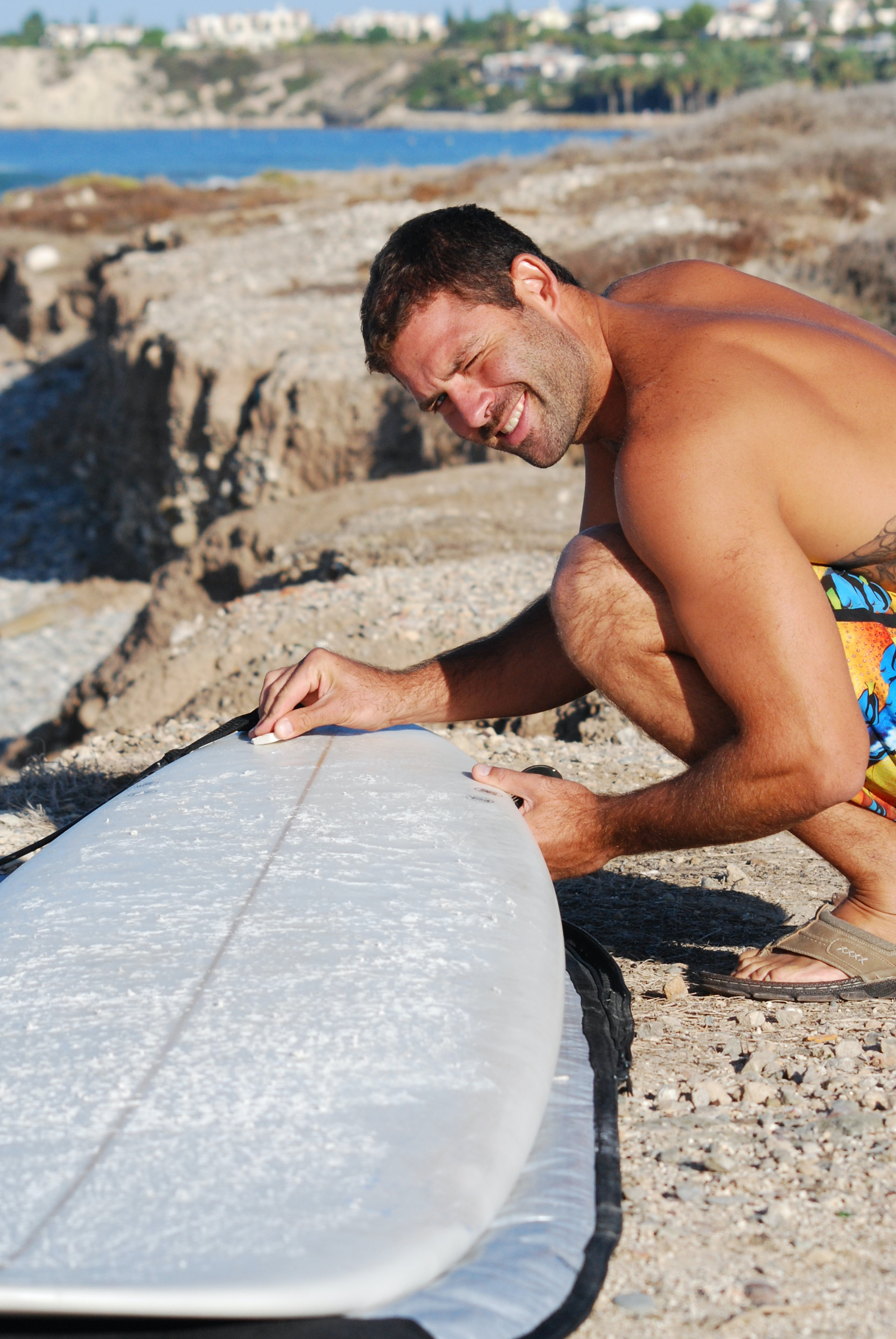 man scraping gray surfboard