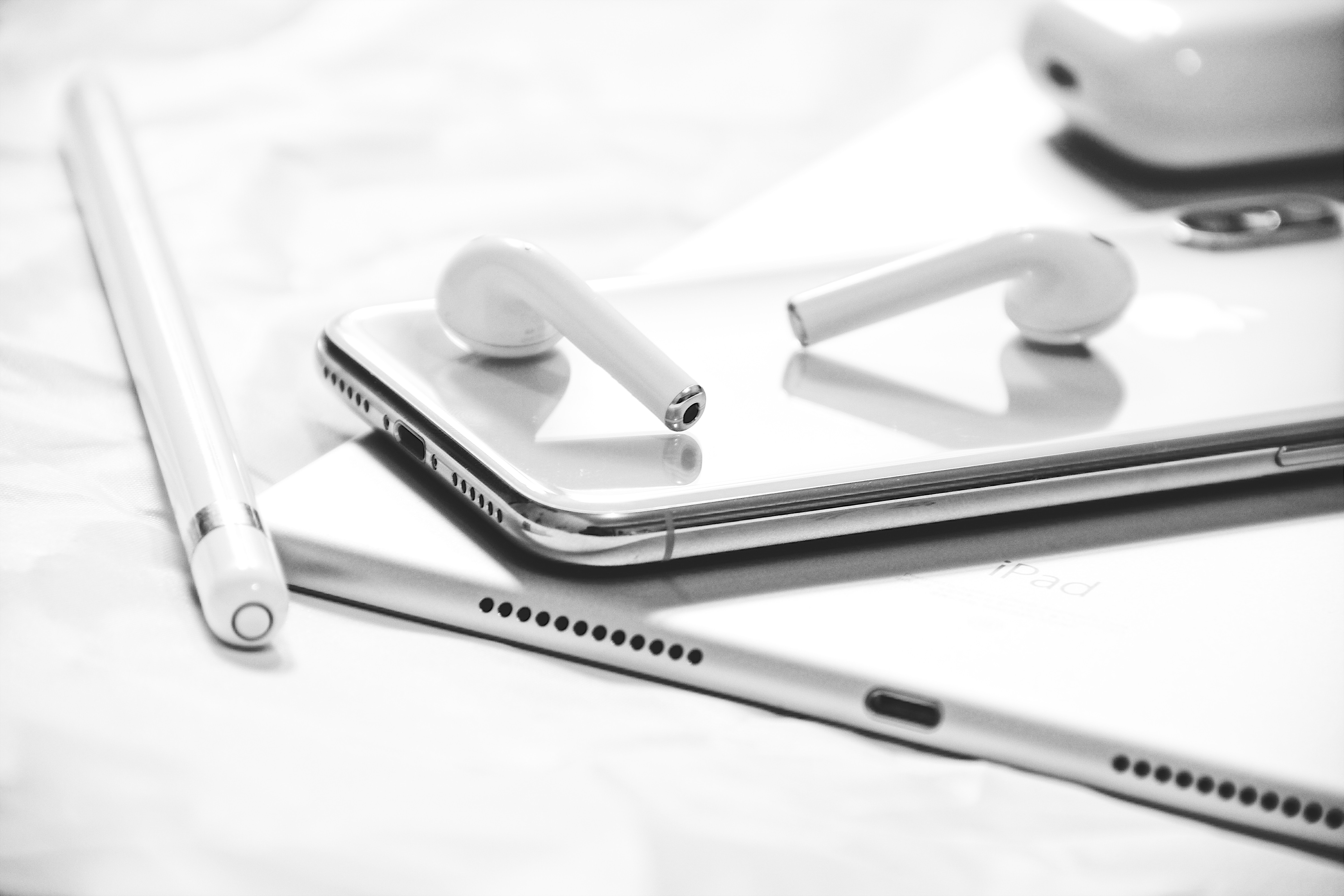 grayscale photography of iPhone X, AirPods, Apple Pencil and iPad