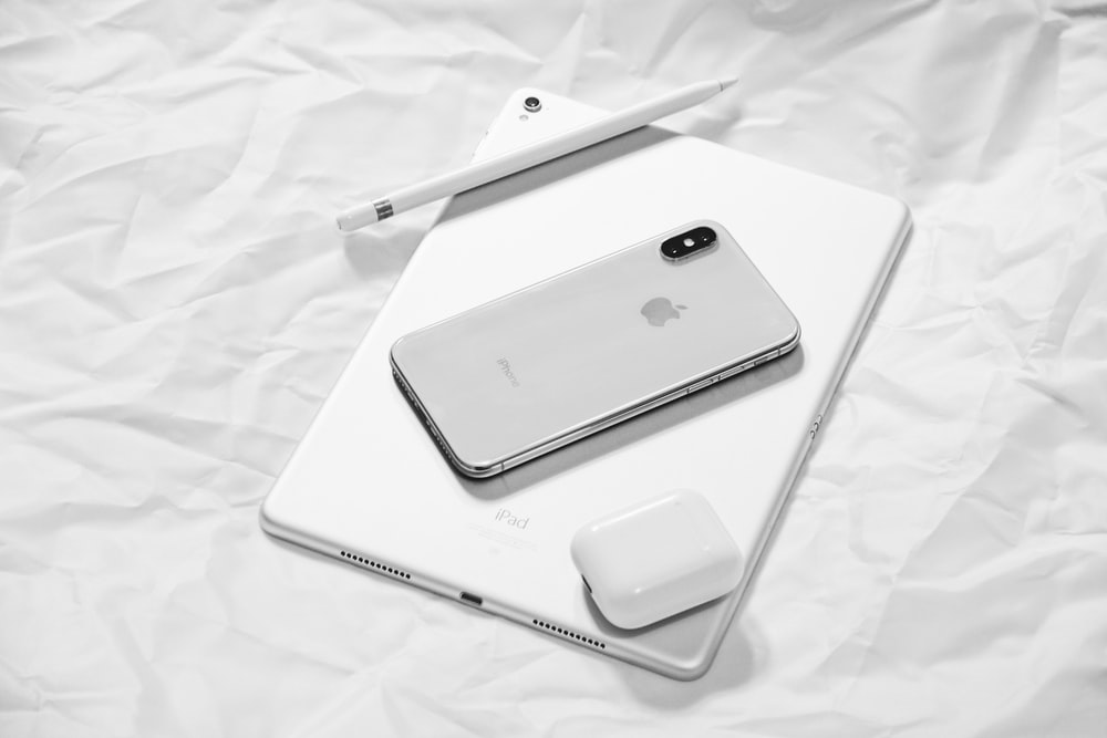 silver iPhone X with silver iPad