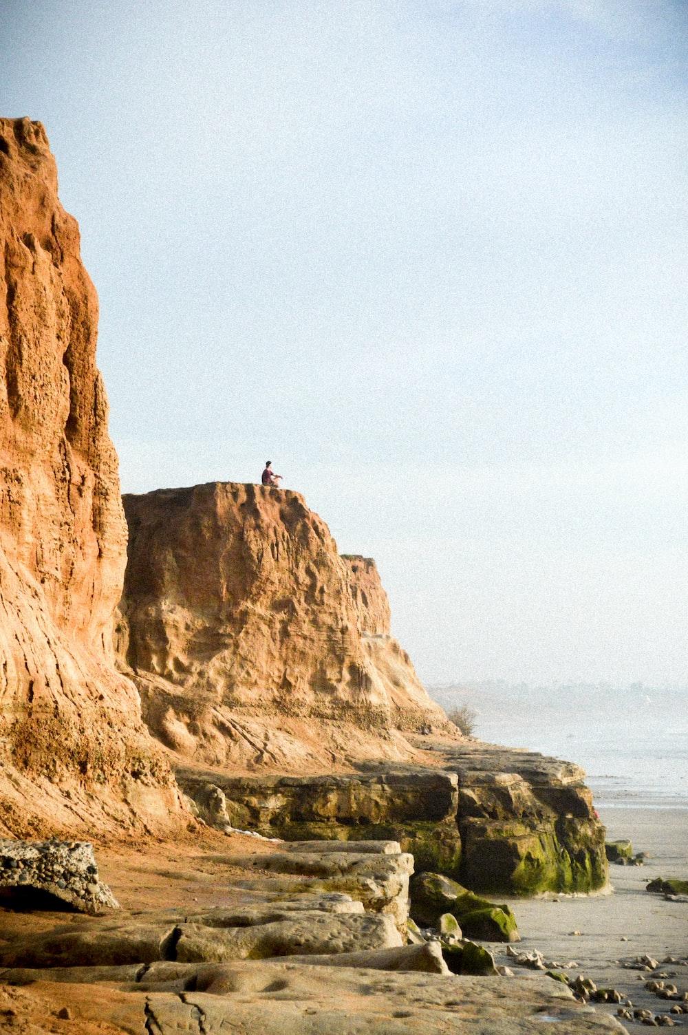 man on cliff near water