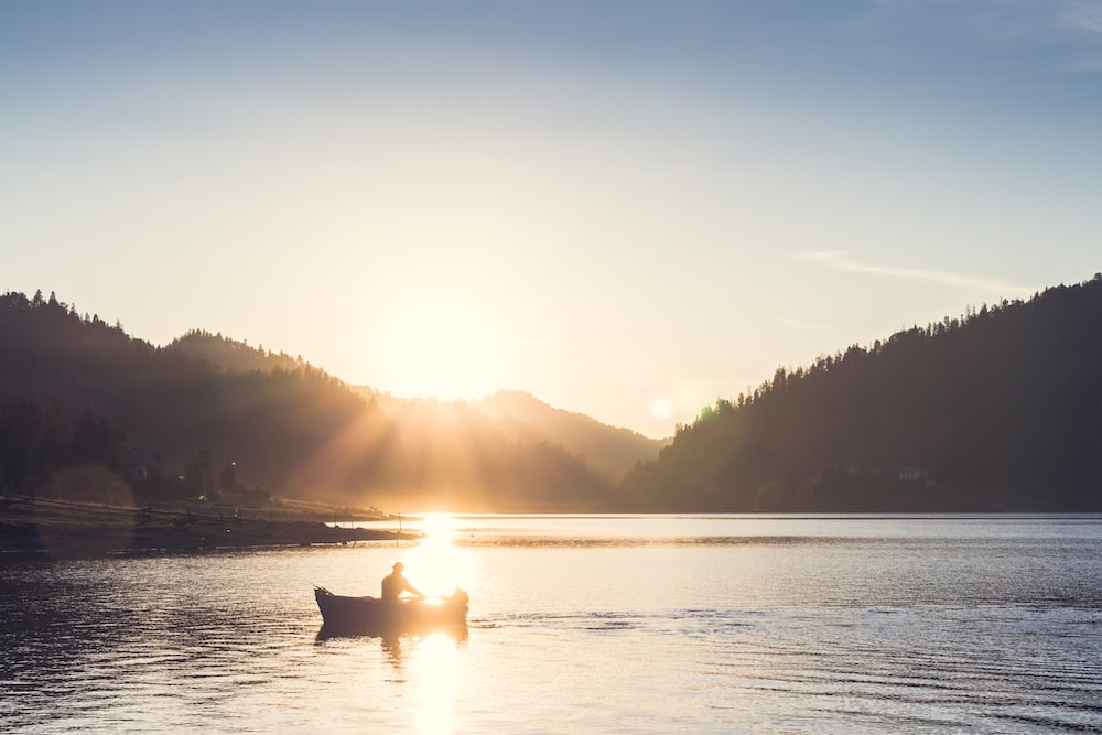 person on boat sailing during sunset