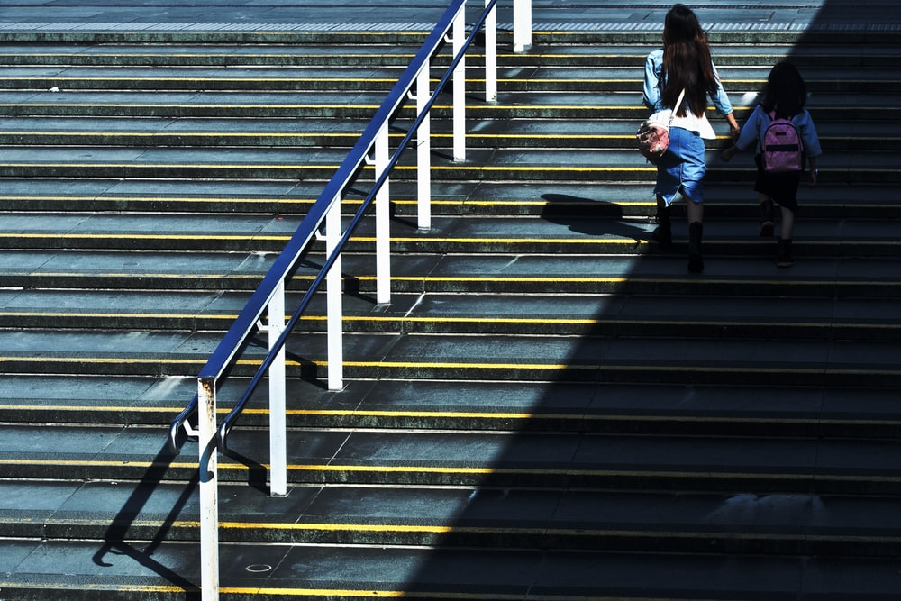 woman holding girl walking on stairs