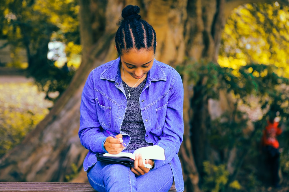 selective focus photography of woman reading book while sitting at bench