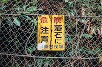 kanji labeled signage hanged on wire fence