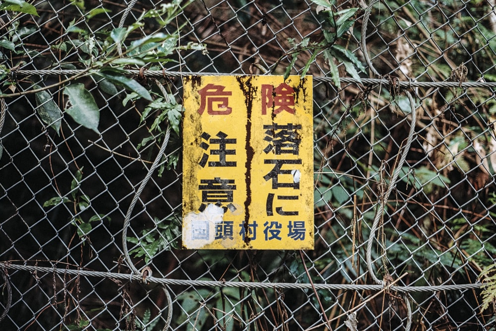 kanji labeled signage hanged on wire fence