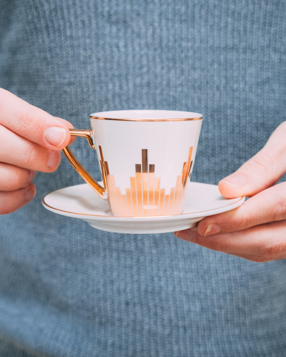 person holding white-and-gold ceramic teacup with saucer