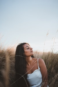 shallow focus photography woman in white spaghetti strap top sitting on brown grasses during orange sunset