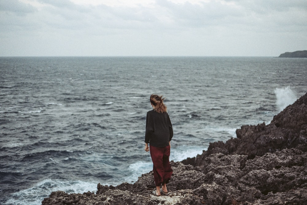woman standing at seashore cliff