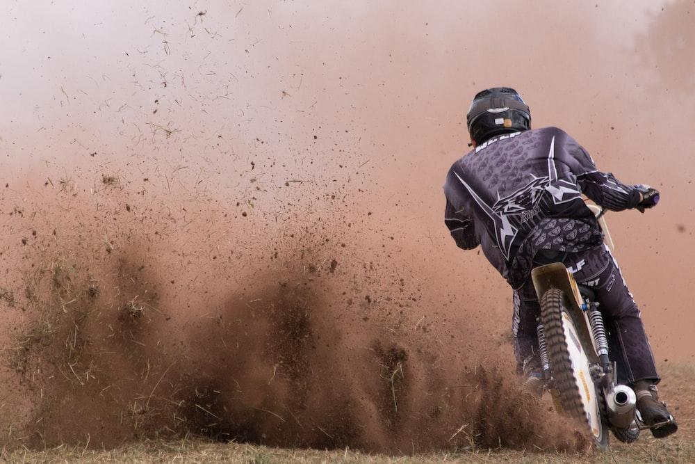 person driving motocross dirt bike during daytime