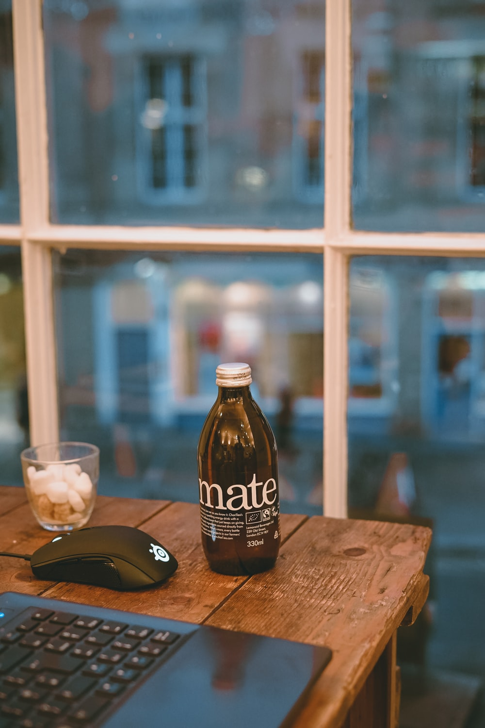 brown glass bottle near drinking glass and laptop on brown wooden table